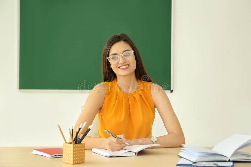 Młody żeński nauczyciel pracuje przy stołem obraz stock