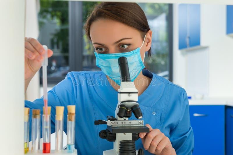 Młody żeński naukowiec jest ubranym maskę w mundurze jest przyglądającym thro obrazy royalty free