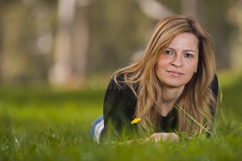 Młody żeński obsiadanie na trawie zdjęcie stock