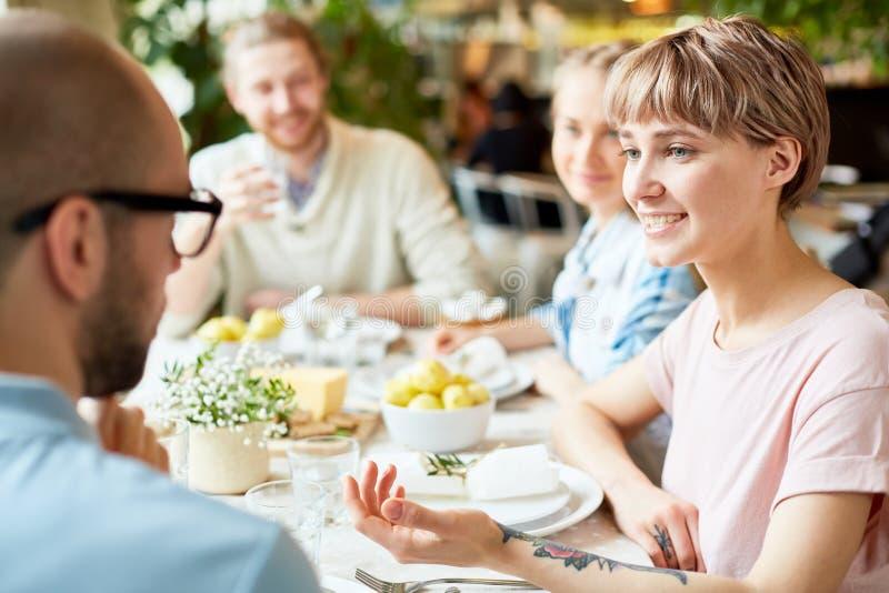 Młody żeński opowiadać z przyjacielem w kawiarni zdjęcie royalty free