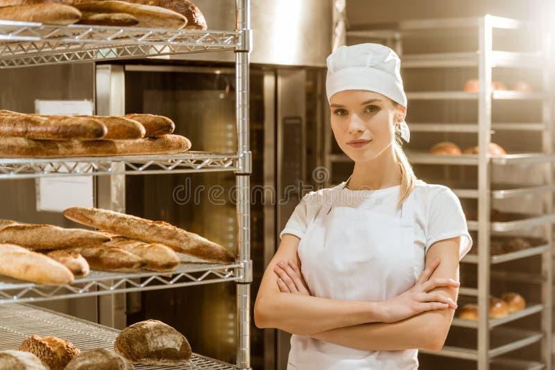 młody żeński piekarz z krzyżować rękami blisko odkłada z świeżo piec chlebem zdjęcia royalty free