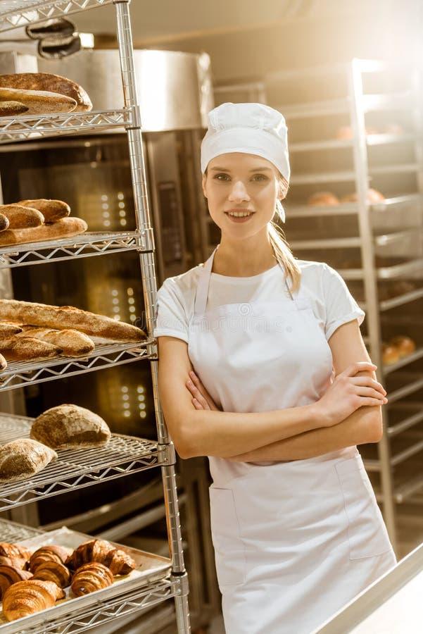 młody żeński piekarz z krzyżować rękami opiera na półkach z świeżo piec chlebem fotografia royalty free