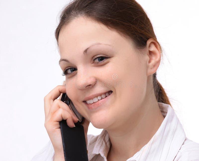 Młody żeński pracownik opowiada na telefonie komórkowym Odizolowywaj?cy na bielu fotografia royalty free