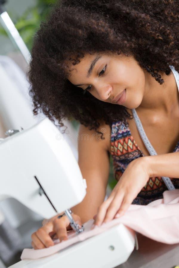 Młody żeński projektant mody pracuje na szwalnej maszynie fotografia royalty free