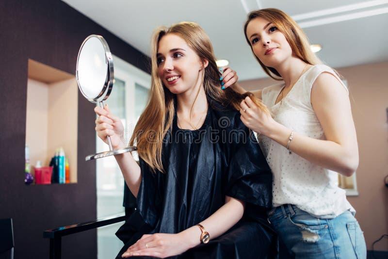 Młody żeński stylista dyskutuje nowy wygląd dla klienta obsiadania na krześle patrzeje w makeup lustrze wewnątrz i wybiera zdjęcie stock