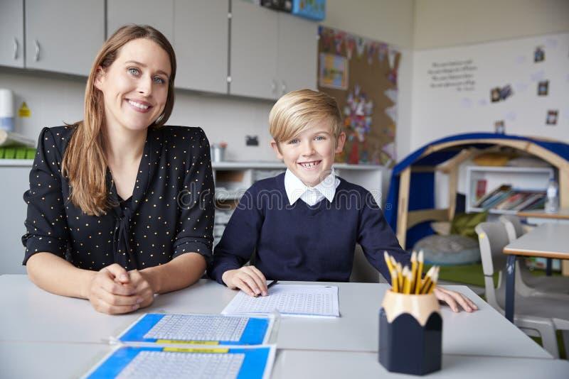 Młody żeński szkoła podstawowa ucznia i nauczyciela obsiadanie przy stołem, pracuje jeden na jeden w sali lekcyjnej, ono uśmiecha zdjęcia stock
