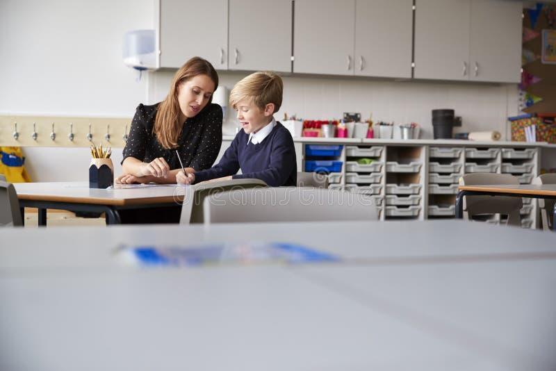 Młody żeński szkoła podstawowa ucznia i nauczyciela obsiadanie przy stołowym działaniem jeden na jeden, selekcyjna ostrość fotografia royalty free