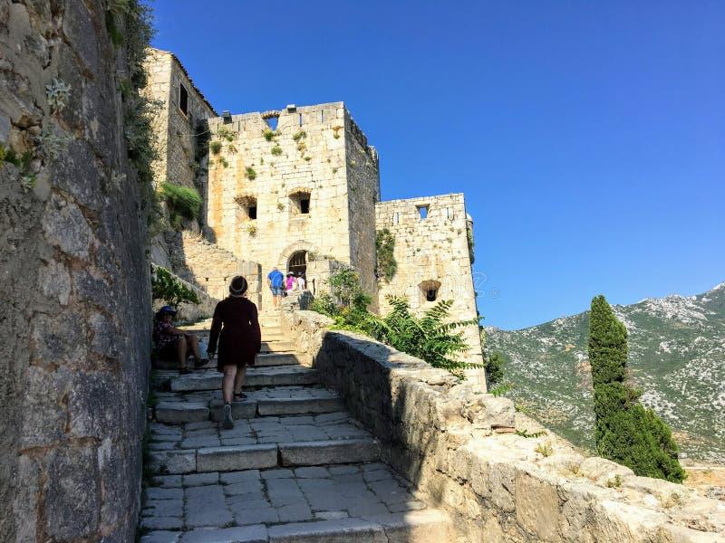 Młody żeński turystyczny odprowadzenie wokoło średniowiecznego fortecy Klis na pięknym letnim dniu zdjęcia stock