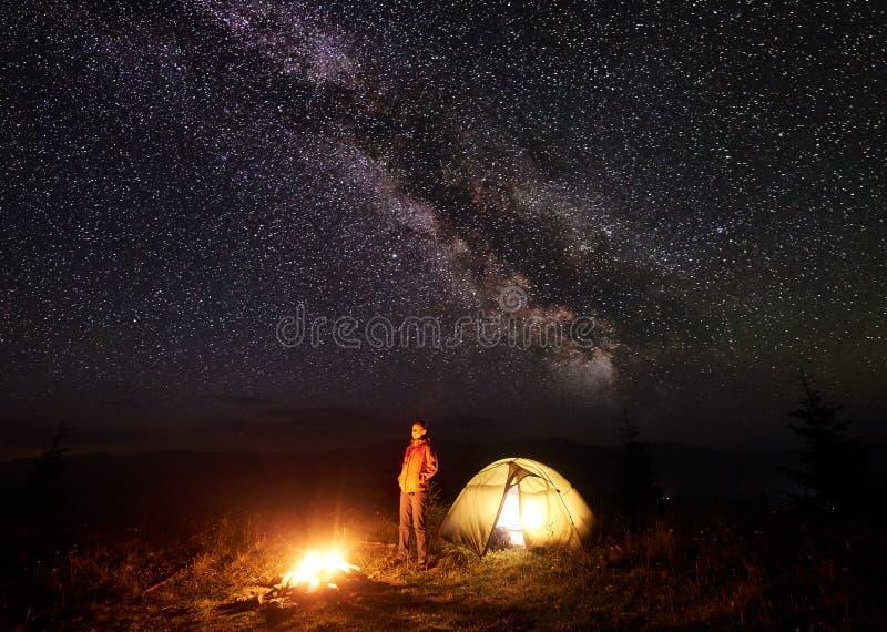 Młody żeński turystyczny trwanie pobliski iluminujący namiot, obozuje w górach przy nocą pod gwiaździstym niebem obraz stock