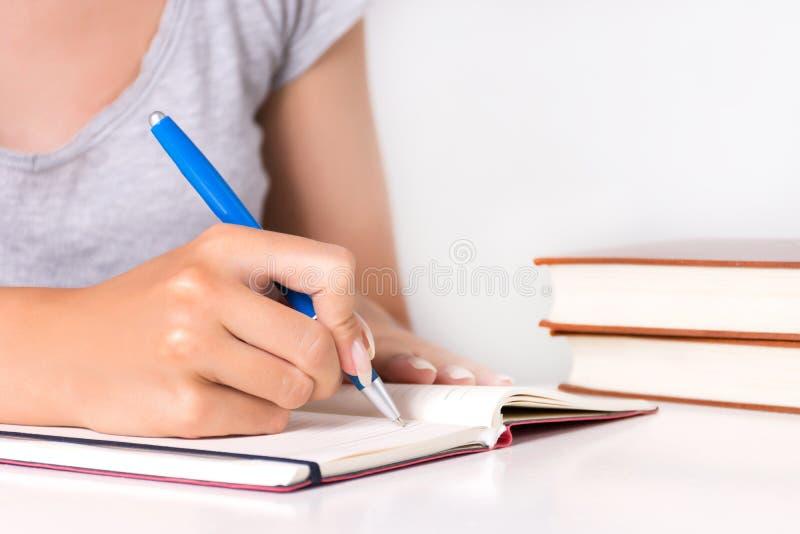Młody żeński uczeń pisze w notatniku na biurku z książką fotografia stock