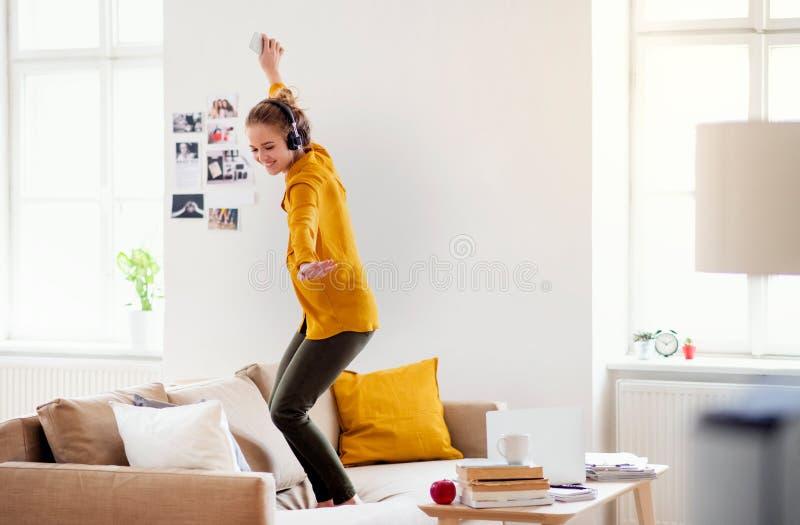 Młody żeński uczeń tanczy na kanapie z hełmofonami gdy studiujący zdjęcie stock