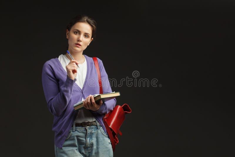 Młody żeński uczeń z książkami i plecakiem zdjęcie royalty free