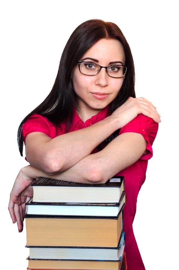 Młody żeński uczeń z szkłami i stertą książki odizolowywać na białym tle fotografia royalty free
