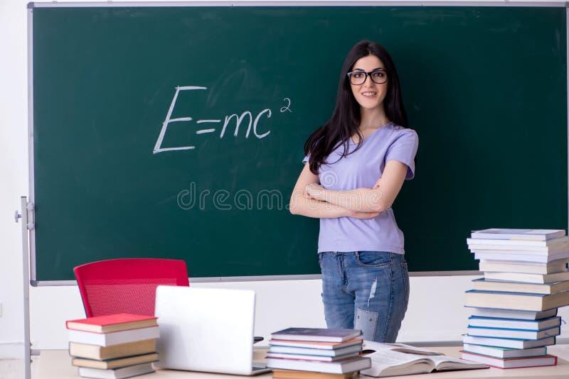 Młody żeńskiego nauczyciela uczeń przed zieleni deską fotografia stock