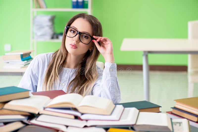 Młody żeńskiego ucznia narządzanie dla egzaminów z wiele książkami fotografia royalty free