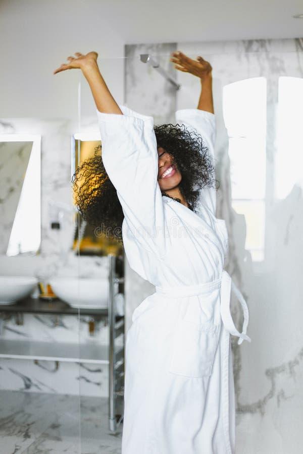 Młody afro amerykański szczęśliwy kobieta taniec w łazience i być ubranym białego bathrobe obraz royalty free