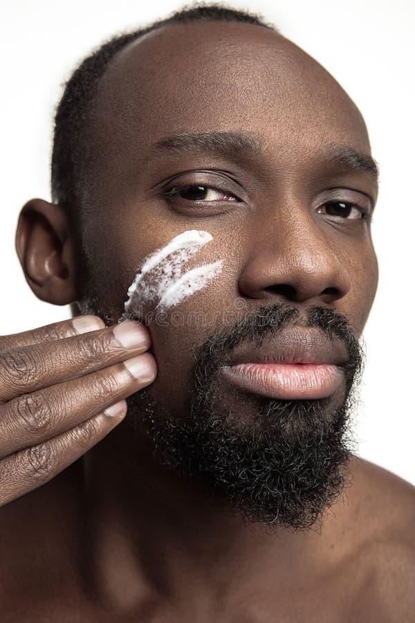 Młody afroamerykański facet stosuje twarzy śmietankę pod jego ono przygląda się na białym tle obraz royalty free