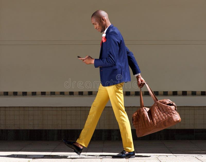 Młody afrykański biznesmen chodzi Wirth telefon komórkowego i torbę zdjęcie royalty free