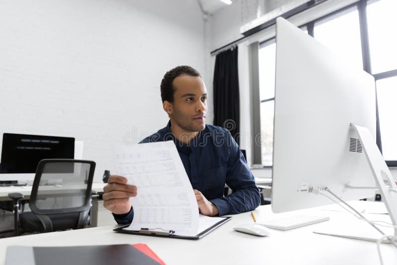 Młody afrykański biznesowego mężczyzna obsiadanie przy jego biurkiem zdjęcia royalty free