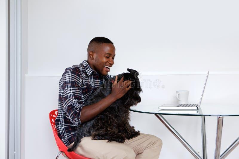 Młody afrykański facet bawić się z jego zwierzę domowe psem obraz royalty free
