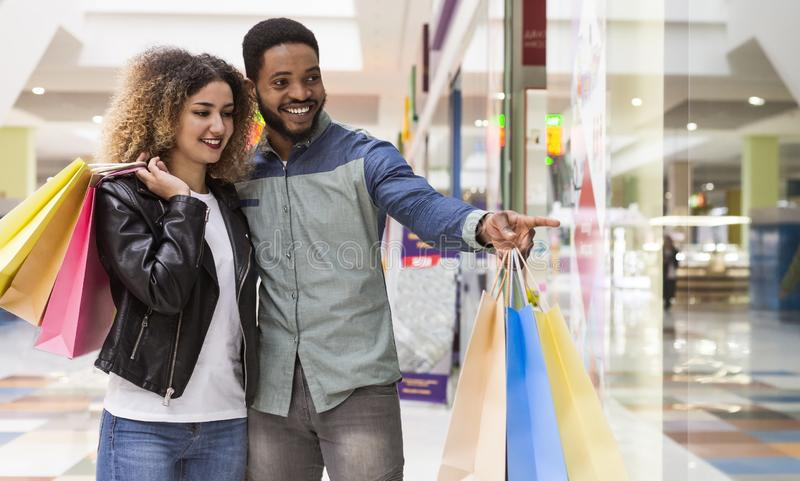 Młody afrykański facet wskazuje z palcem przy zakupy okno zdjęcia royalty free