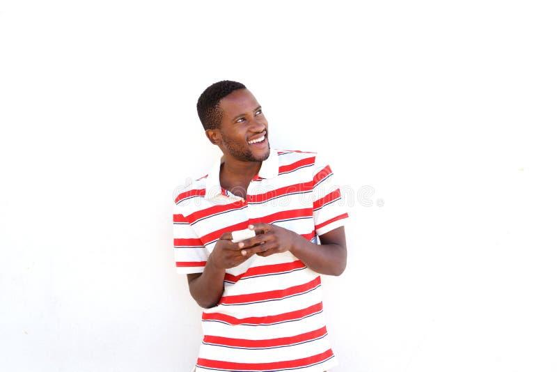 Młody afrykański mężczyzna patrzeje daleko od z telefonem komórkowym obraz stock