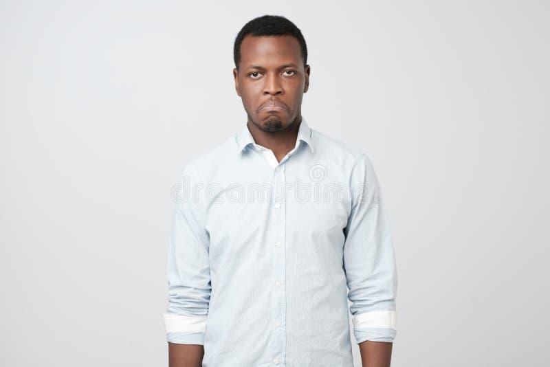 Młody afrykański mężczyzna patrzeje smutnym i obrażać, marszczyć brwi brwi, wargi pout, są ubranym, białą koszula obraz stock