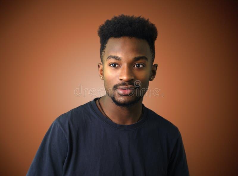 Młody afrykański mężczyzna portreta brązu gradientu tło zdjęcia royalty free