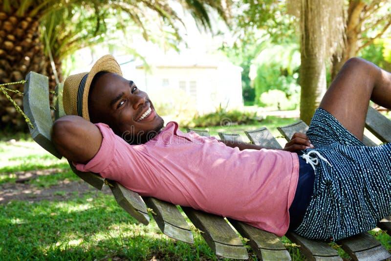 Młody afrykański mężczyzna relaksuje outdoors na hamaku zdjęcie stock