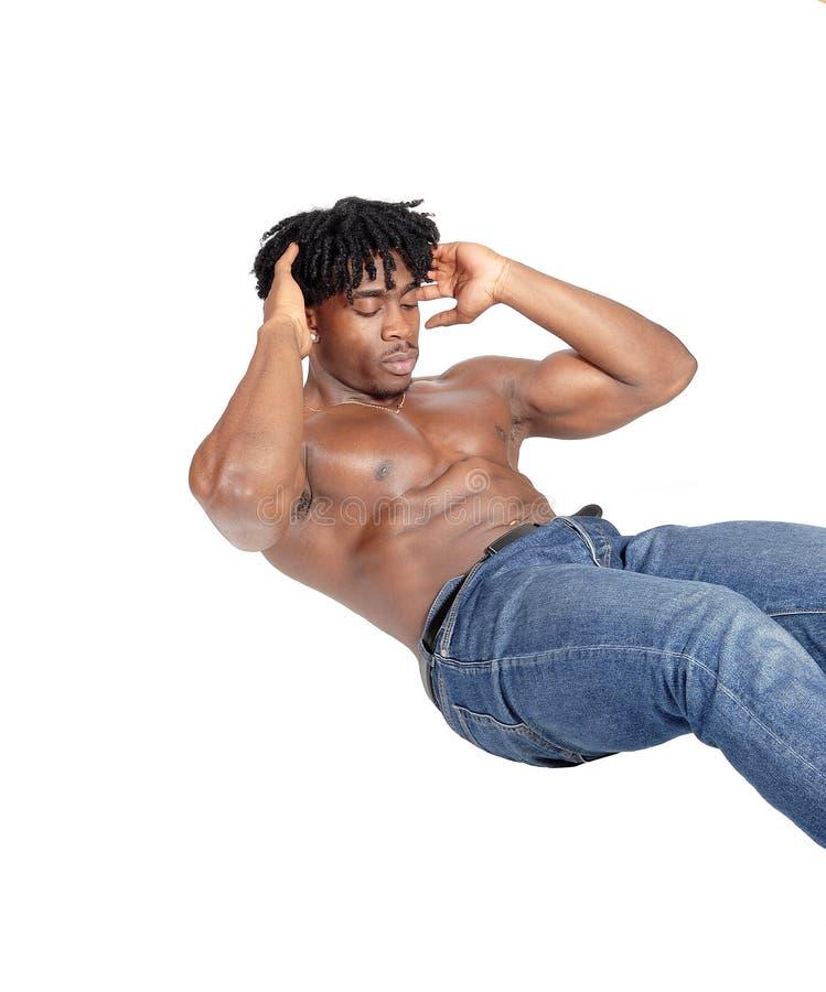 Młody Afrykański mężczyzna ups obsiadanie na podłogowy robić pcha obraz royalty free