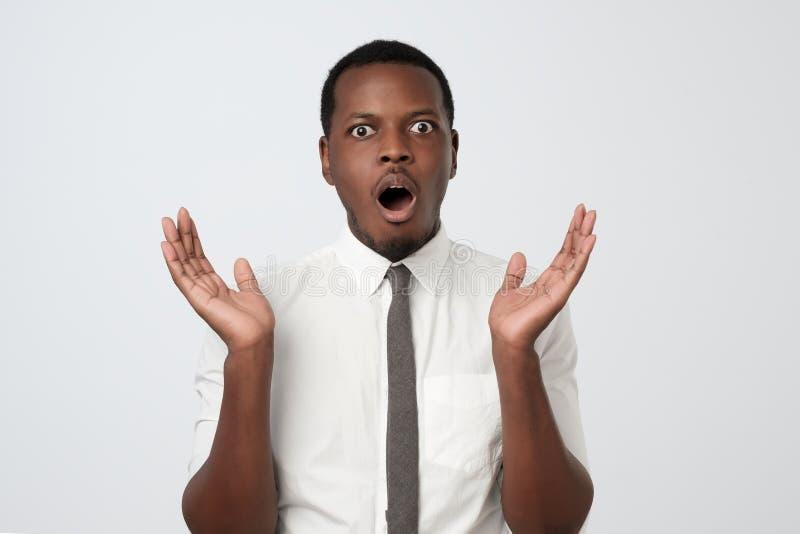Młody afrykański mężczyzna w białej koszula, doświadczający głębokiego zdziwienie i strach fotografia royalty free