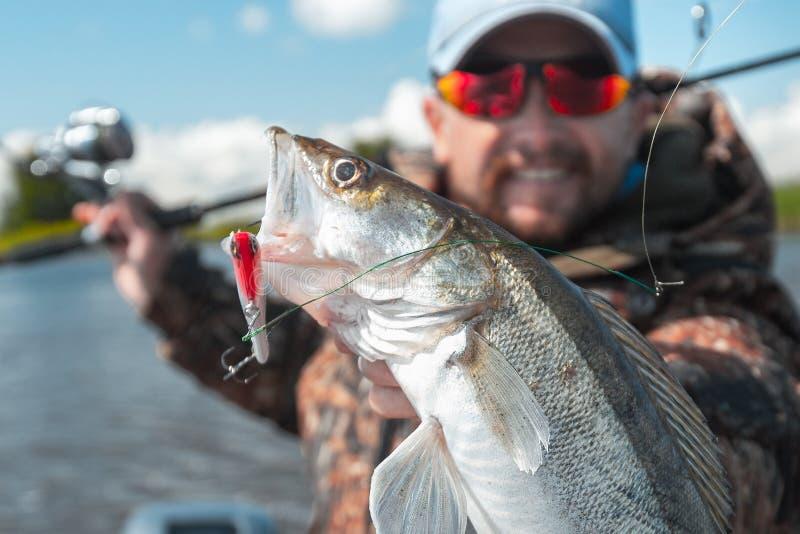 Młody amator wędkarz trzyma rybę fotografia stock