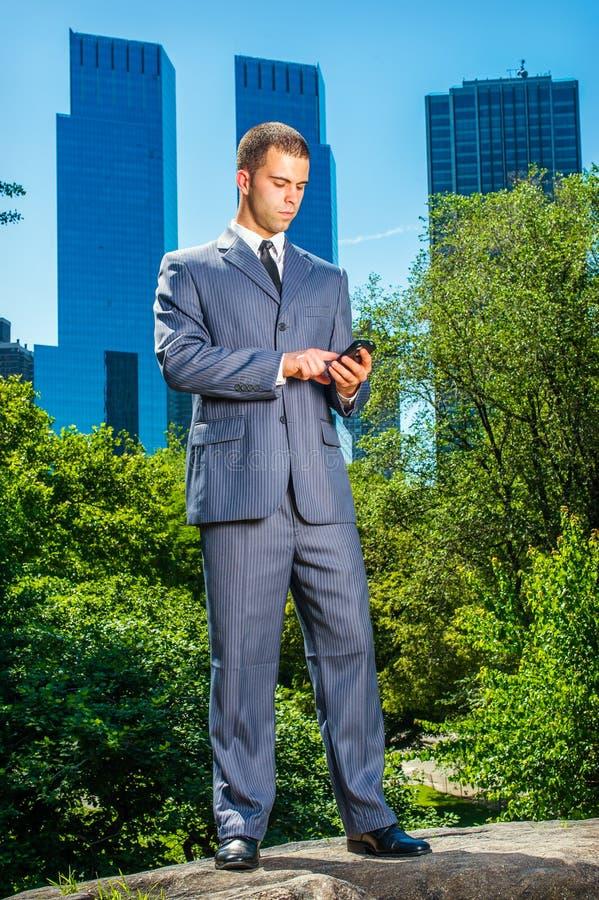 Młody Amerykański biznesmen texting na telefonie komórkowym, podróżuje, wor obraz stock