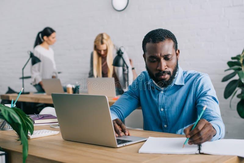 młody amerykanin afrykańskiego pochodzenia biznesmen pisze w podręczniku i używa laptop przy pracować stołu i dwa bizneswomanów obraz royalty free