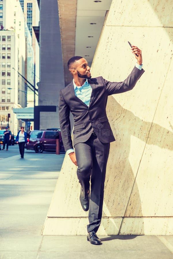 Młody amerykanin afrykańskiego pochodzenia biznesmen z brodą, rozciągający rękę, bierze selfie na telefonie komórkowym na zewnątr fotografia royalty free