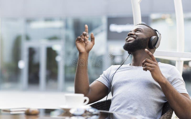 Młody amerykanin afrykańskiego pochodzenia facet cieszy się muzykę w hełmofonach obraz stock