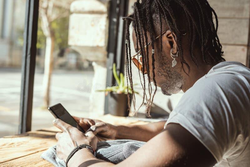 Młody amerykanin afrykańskiego pochodzenia patrzeje i pisać na maszynie z telefonem komórkowym obraz stock