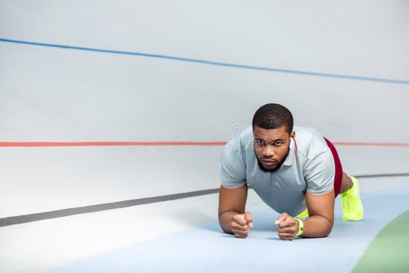Młody amerykanin afrykańskiego pochodzenia sportowiec robi deski ćwiczeniu zdjęcie royalty free