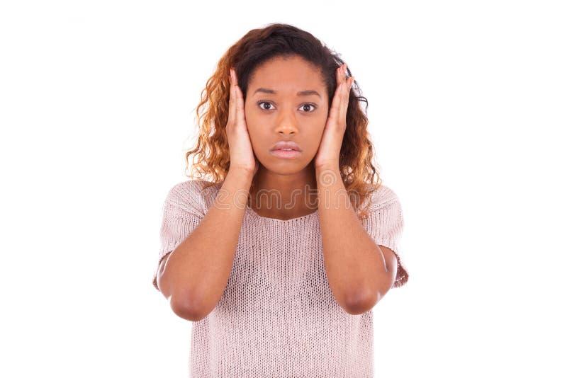Młody amerykanin afrykańskiego pochodzenia zakrywa jej ucho z jej rękami odizolowywać obraz stock