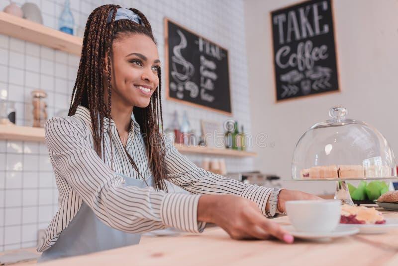 Młody amerykanina afrykańskiego pochodzenia barista słuzyć filiżankę kawy fotografia stock