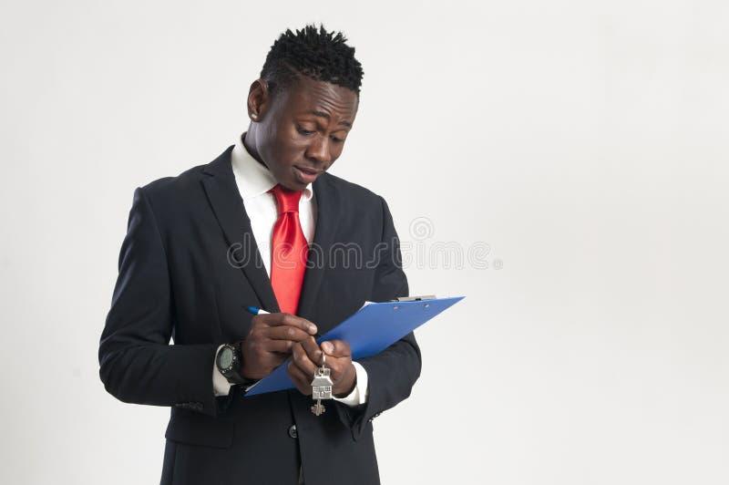 Młody amerykanina afrykańskiego pochodzenia biznesmen trzyma domowego klucz obrazy stock