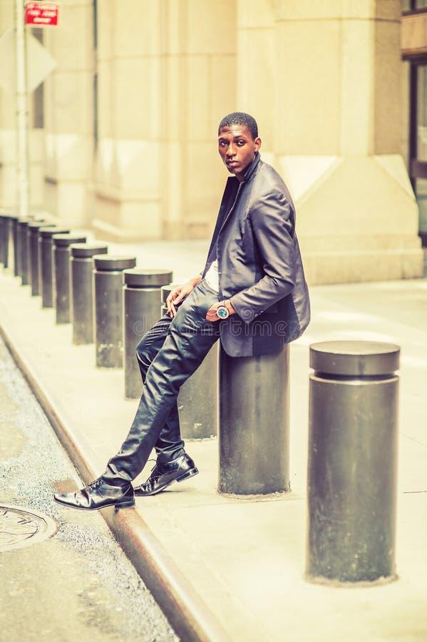 Młody amerykanina afrykańskiego pochodzenia mężczyzna obsiadanie na ulicie w Nowy Jork, relaxi obraz royalty free