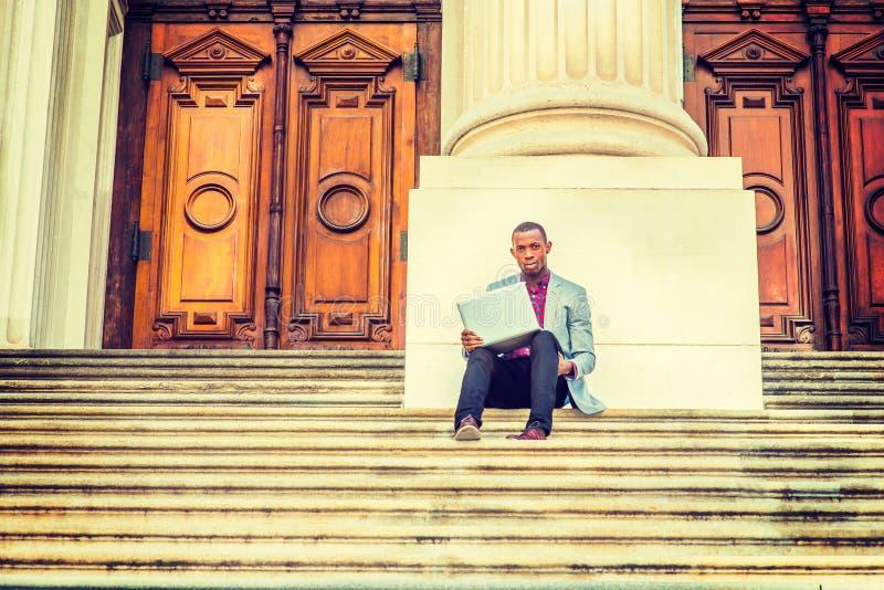 Młody amerykanina afrykańskiego pochodzenia mężczyzna pracuje na laptopie outside wewnątrz fotografia stock