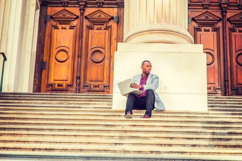 Młody amerykanina afrykańskiego pochodzenia mężczyzna pracuje na laptopie outside wewnątrz zdjęcia royalty free