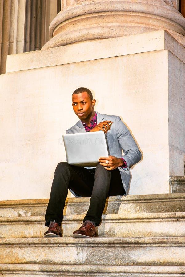 Młody amerykanina afrykańskiego pochodzenia mężczyzna pracuje na laptopie outside wewnątrz fotografia royalty free