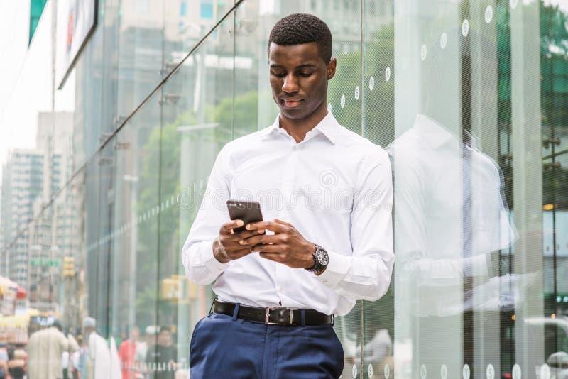 Młody amerykanina afrykańskiego pochodzenia mężczyzna texting na telefonie komórkowym, podróżuje w N zdjęcie royalty free