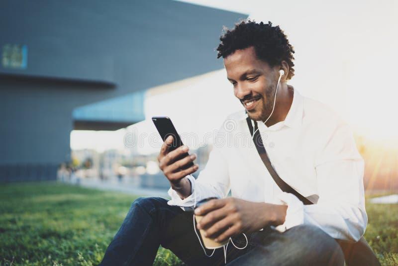 Młody amerykanina afrykańskiego pochodzenia mężczyzna w hełmofonu obsiadaniu przy pogodnym miasto parkiem i cieszyć się słuchać m obrazy stock