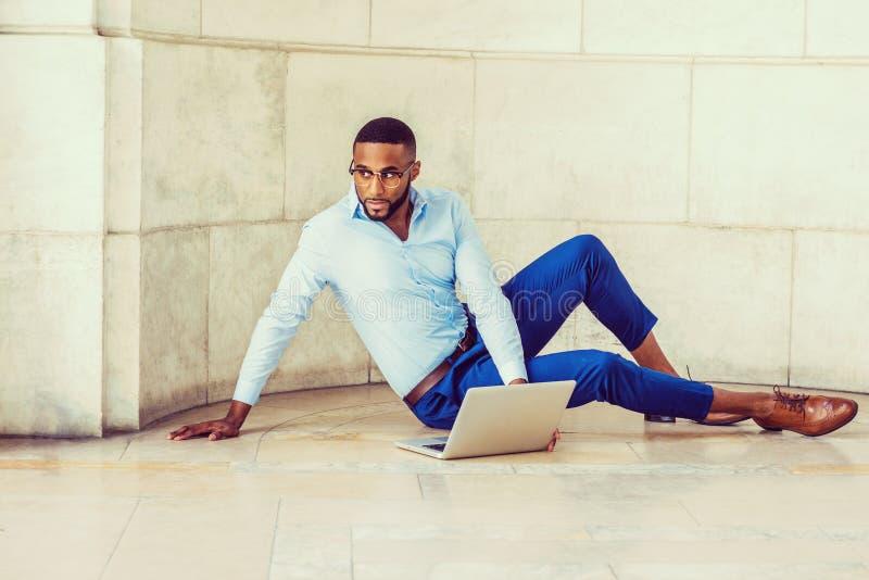 Młody amerykanina afrykańskiego pochodzenia mężczyzna z brodą pracuje na laptopie zdjęcie royalty free