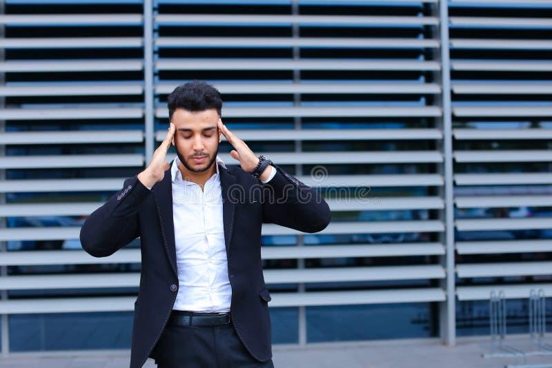 Młody arabski mężczyzna pokazuje szyja ból męczącego w centrum biznesu fotografia stock
