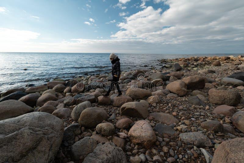 Młody archeolog na głazu plażowym szuka egzocie kołysa na linii brzegowej morze bałtyckie fotografia royalty free